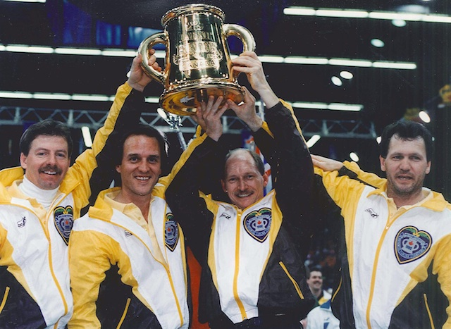 The 1992 Brier champions hoist the trophy. From left, Vic Peters, Dan Carey, Chris Neufeld and Don Rudd (CCA photo)