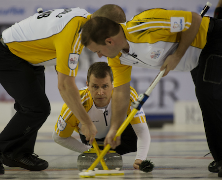 Manitoba skip Jeff Stoughton delivers his rock to sweepers Mark Nichols, left, and Reid Carruthers.