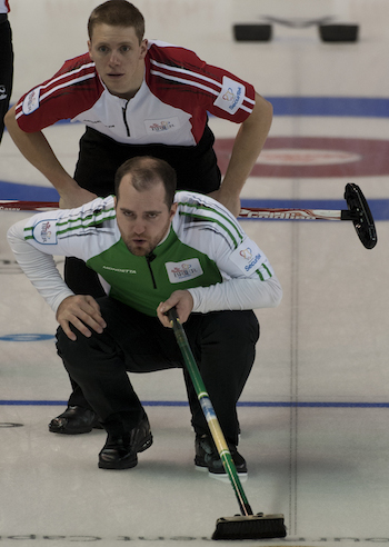 Saskatchewan skip Steve Laycock, front, watches his shot as Newfoundland/Labrador's Adam Casey looks on.