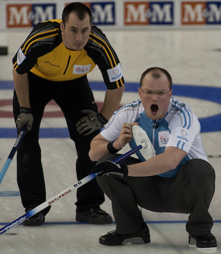 Quebec vice-skip Martin Crête, right, shouts to his sweepers as New Brunswick second Darren Roach looks on