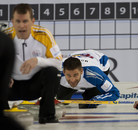 B.C. skip John Morris gets low to watch the line of a Manitoba shot.
