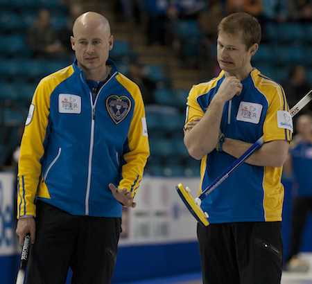 Alberta skip Kevin Koe, left, and second Carter Rycroft discuss strategy.
