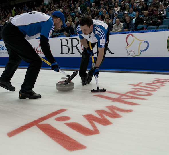 B.C.'s Jim Cotter, left, and Rick Sawatsky sweep a rock during Thursday night's game. (Photos, CCA/Michael Burns)