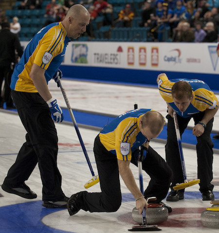 Alberta's Nolan Thiessen, left, and Carter Rycroft, right, urge teammate Pat Simmons to sweep even harder