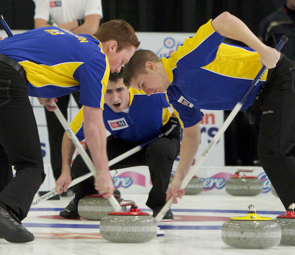 Alberta skip Carter Lautner, middle, encourages sweepers Kyle Morrison, left, and David Aho. (Photo, CCA)