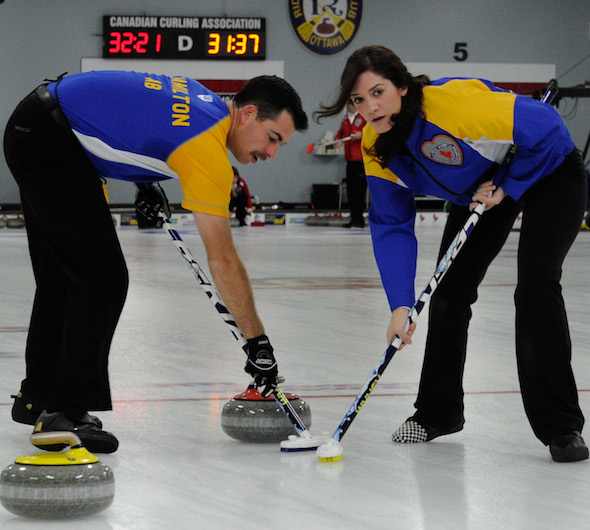 Alberta sweepers Brent Hamilton, left, and Heather Jensen work a rock during their win over the Territories on Tuesday.  (Photo, CCA/Claudette Bockstael, Studio C Photography)
