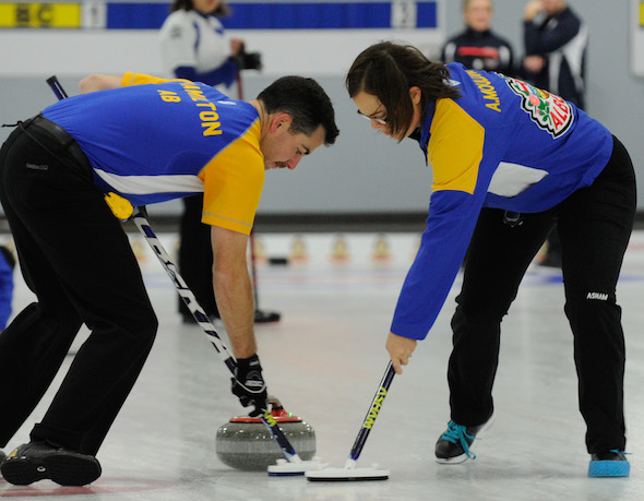 Alberta's front end of Brent Hamilton, left, and Anna-Marie Moulding work a rock during their team's win on Wednesday afternoon. (Photo, CCA/Claudette Bockstael, Studio C Photography)