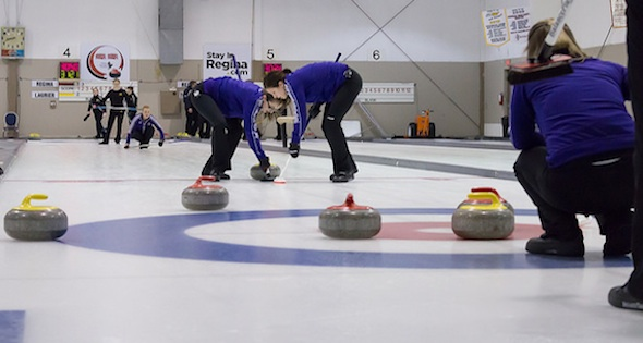 Wilfrid Laurier University sweepers hard at work on the ice at the Callie Curling Club in Regina (Photo CIS University Championships)