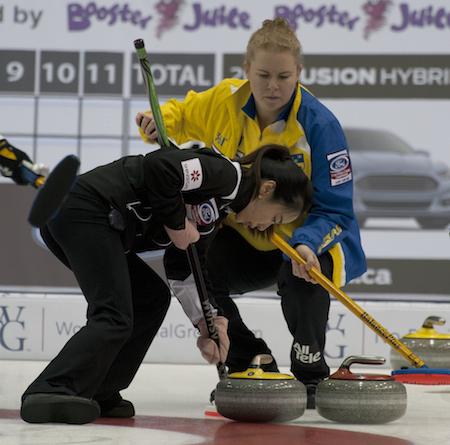 South Korean skip Ji-sun Kim sweeps a rock as Swedish skip Margaretha Sigfridsson looks on. (Photo, CCA/Michael Burns)