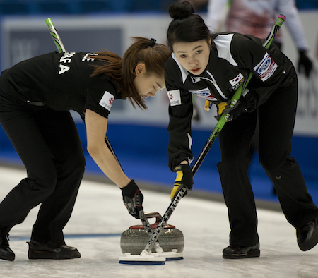 South Korean sweepers Seulbee Lee, left, and Min Ji Um work on a rock during their win over Latvia. (Photo, CCA/Michael Burns)