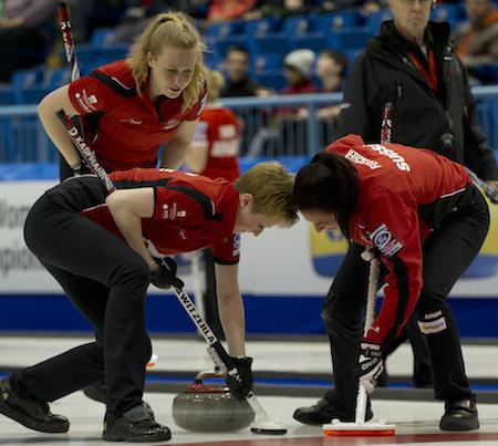 Team Switzerland third Irene Schori, left, encourages sweepers Franziska Kaufmann, middle, and Christine Urech. (Photo, CCA/Michael Burns)