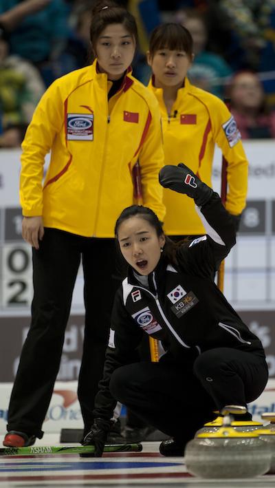 South Korean skip Ji-sun Kim shouts instructions to sweepers as China's Sijia Liu, left, and Jiang Yilun look on. (Photo, CCA/Michael Burns)