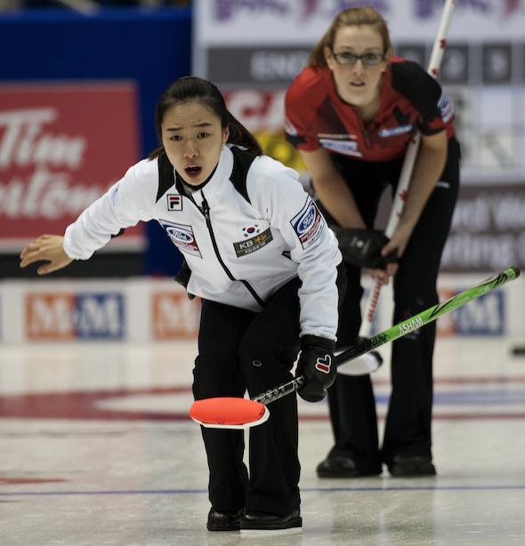 South Korea skip Ji-sun Kim watches her shot as Team Canada's Alison Kreviazuk looks on. (Photo, CCA/Michael Burns)