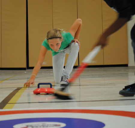 A child tries out curling at a Rocks & Rings visit to her school.