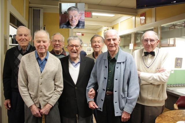 Les nonagénaires des Tam Heather Venerables ont été mis à l'honneur à la fin de la saison 2013-2014 (de gauche à droite): Monte Miller (92), Bob McCowan, (96), Bill Wood (90), Ross Ellis (90), Gord Ramsay (90), Morley Lumby (94), Alex Smith (90), et un membre absent, récemment blessé dans une chute, mais présent dans les cœurs de tous : Bill Reid (photo en médaillon, 95 ans), (photo soumise par A. Lamb)