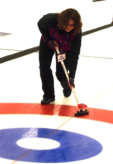 Lisa Shamchuk tries out a training broom that measures sweeping speed and pressure. (Photo by Lisa Shamchuk)