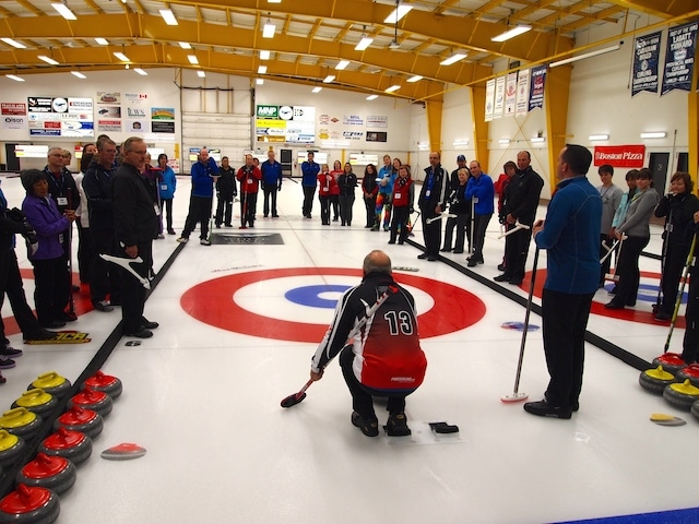 Participants observe as Paul Webster and Andy Jones demonstrate a proper curling delivery. (Photo by Lisa Shamchuk)]