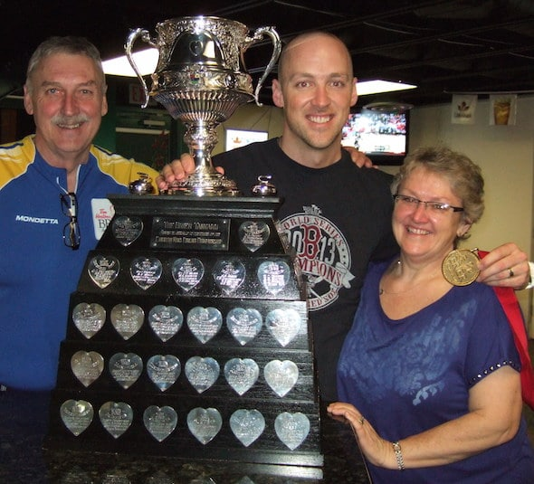 Nolan Thiessen, middle, shows off the Tim Hortons Brier Tankard with parents Bill and Debbie following his team's win last March in Kamloops, B.C. (Photo, courtesy Thiessen family)