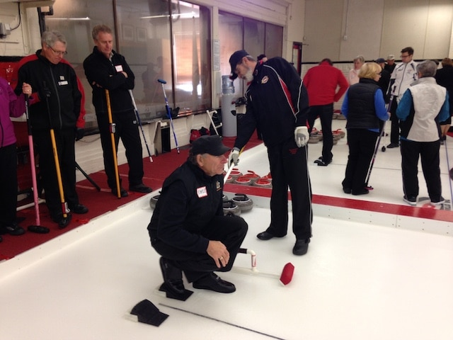 Earle Morris plays the part of a novice curler while instructor Michel St. Marseille adjusts his position in the hack during the Train the Trainer session (Photo courtesy Ottawa Curling Club)