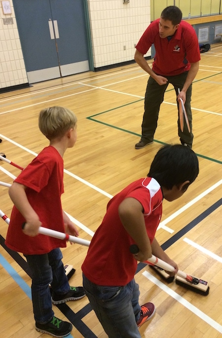 Students get some sweeping tips from Olympic gold-medallist John Morris. (Photo, CCA)