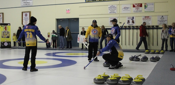 Bill Pearce readies himself in the hack to deliver his final stone in the 288th end to his Team Radio for Radiology teammates Andrew Vanbodegom (left) and Brittany Pearce (far right) as Jeff Vanbodegom (standing centre) looks on (Photo Clarissa Yahn)