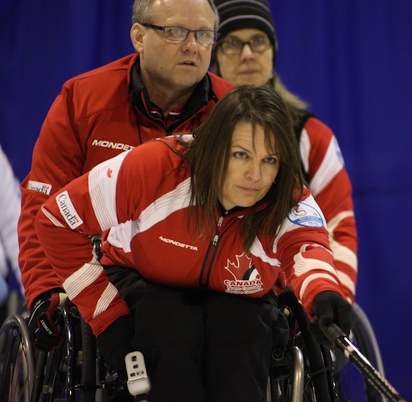 Ina Forrest , front, delivers her rock, as teammates Dennis Thiessen, left, and Sonja Gaudet look on. (Photo, World Curling Federation/Alina Pavlyuchik)