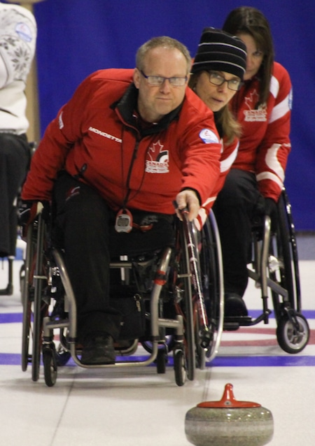 Dennis Thiessen, front, delivers his rock as Sonja Gaudet and Ina Forrest look on. (Photo, World Curling Federation/Alina Pavlyuchik)