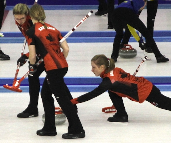 Team Canada lead Jessica Armstrong delivers rock to sweepers Lynn Kreviazuk and Lauren Horton during Day 1 action on Thursday in Granada, Spain. (Photo, Ben Matchett, CIS)