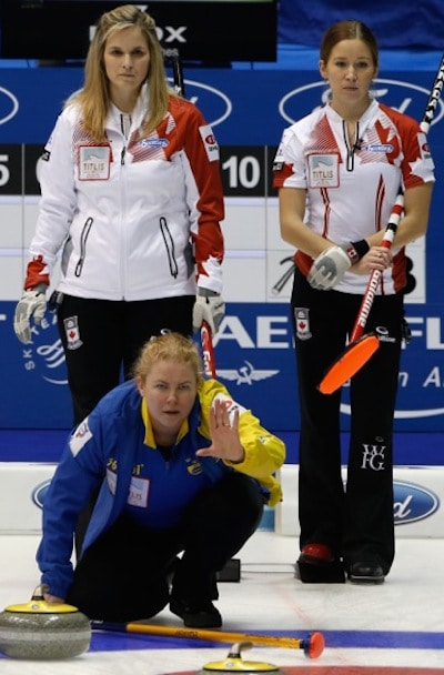 Swedish skip Margaretha Sigfridsson guides her sweepers as Canada's Jennifer Jones, left, and Kaitlyn Lawes look on. (Photo, WCF/Richard Gray)