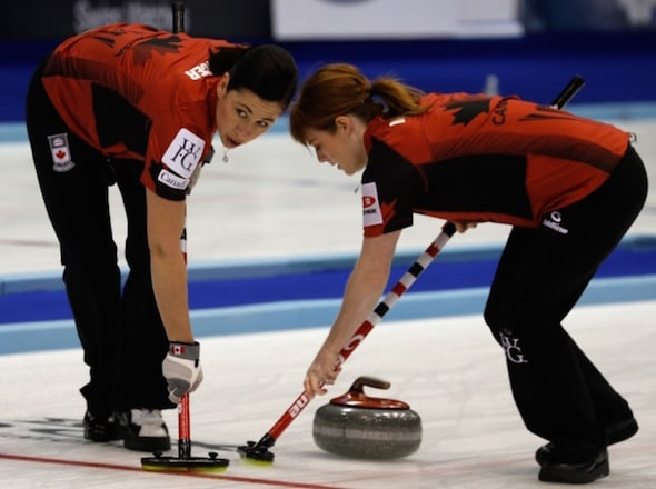 Team Canada's Jill Officer, left, and Dawn McEwen sweep a rock during Monday's win over China. (Photo, WCF/Richard Gray)