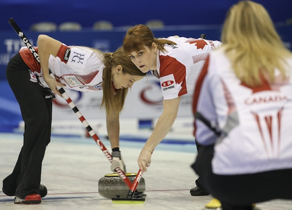 Canada's Kaitlyn Lawes, left, and Dawn McEwen sweep a rock as Jennifer Jones gives instructions. (Photo, WCF/Richard Gray)