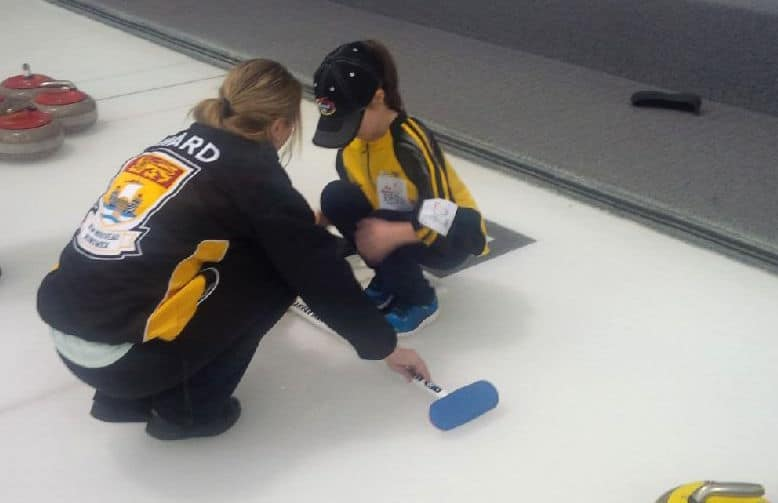 Curler and Rocks & Rings instructor Cathlia Ward offers a curling lesson to a young curler during a break at the 2015 Canadian Mixed Curling Championship in North Bay, Ont. (Photo courtesy Cathlia Ward)