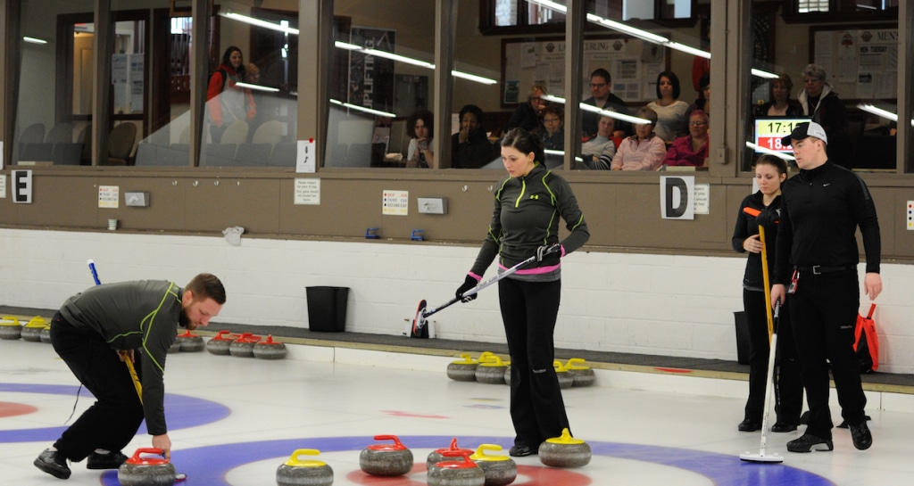Charley Thomas sweeps a rock into the rings, watched by teammate Kalynn Park and opponents Bowie Abbis-Mills and Tess Bobbie during the final of the 2015 Mixed Doubles Curling Trials at the Ottawa Hunt & Golf Club (Claudette Bockstael photo)