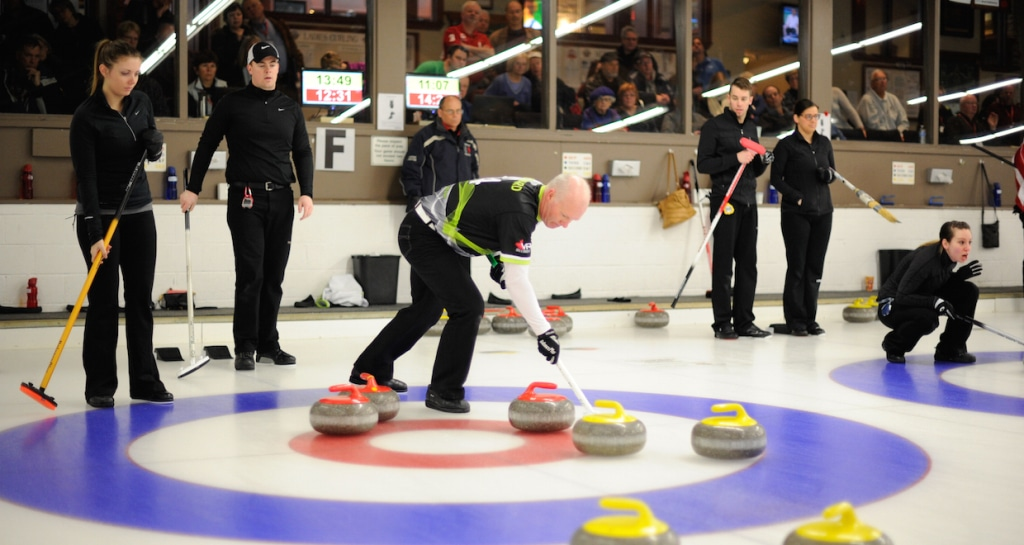 Tess Bobbie and Bowie Abbis-Mills (left) watch as Glenn Howard sweeps a rock in the house during action at the Ottawa Hunt and Golf Club (Photo Claudette Bockstael)
