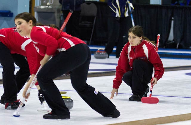 Spare Diamond Wilson, wearing Team NL third Chantal Newell's jacket, delivers her rock during round-robin play at the 2015 Canada Winter Games in Prince George (Photo Vanessa Wilson)