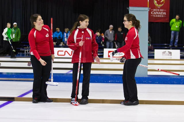 Prince George curler Diamond Wilson laughs with temporary teammates Lauren Barron and Sydney Parsons of Team Newfoundland and Labrador during action at the 2015 Canada Winter Games (Photo Vanessa Wilson)