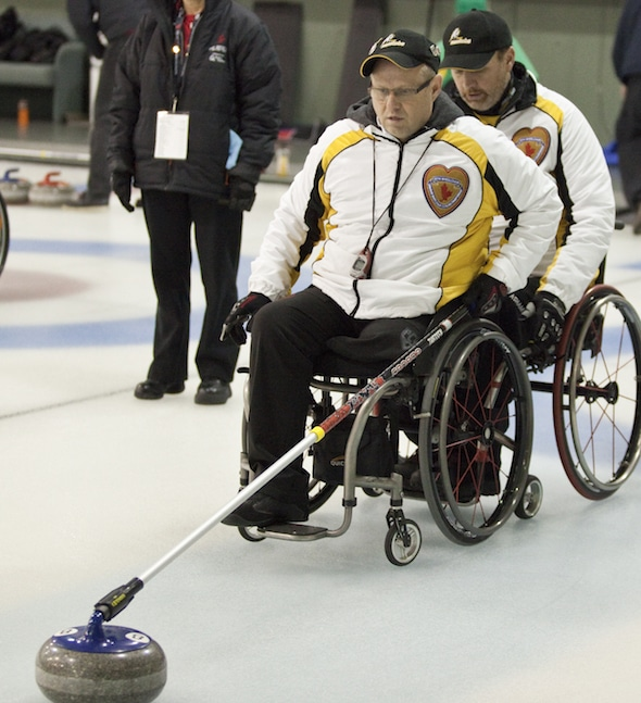 Manitoba skip Dennis Thiessen, left, prepares to deliver stone with backing from teammate Mark Wherrett at the 2014 Canadian Wheelchair Curling Championship.