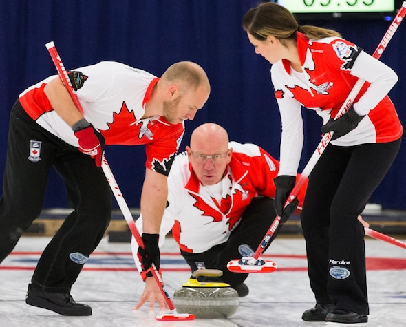 Max Kirkpatrick, centre, delivers rock to sweepers Chris Haichert, left, and Teejay Haichert at the World Mixed Curling Championship in Berne, Switzerland. (Photo, WCF/Céline Stucki)