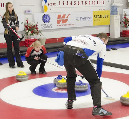 Derek Samagalski, right, sweeps a rock while getting directions from partner Sherry Just during their semifinal loss to Homan and Morris.