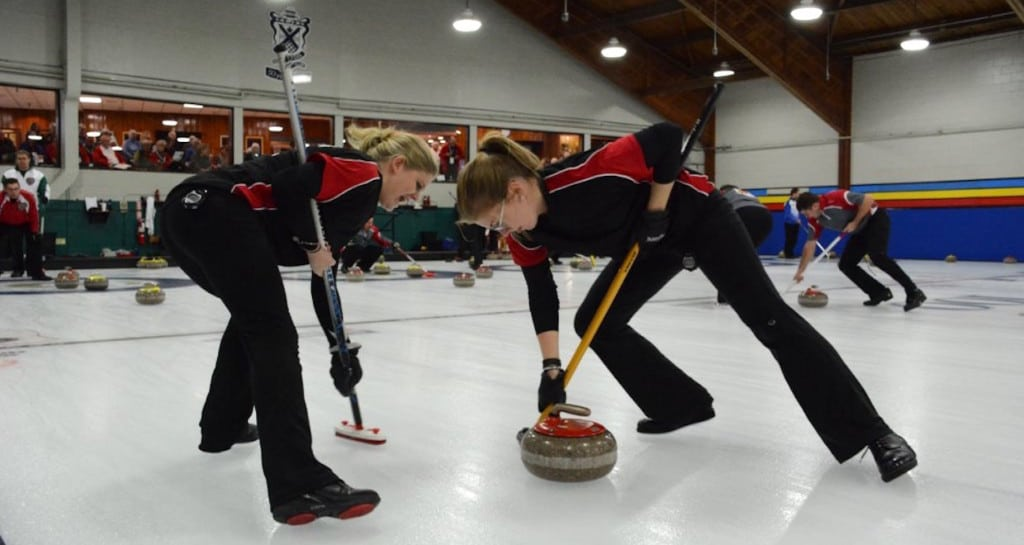 Marie Christianson and Lauren Wasylkiw (NL) sweep hard during the 2016 Canadian Mixed Curling Championship in Toronto (Curling Canada/Sonja DiMarco Photo)