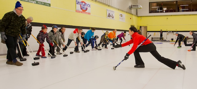 Instructor Abbie Darnley demonstrates delivery techniques to participants in the Curling Canada Rocks & Rings session at the Stroud Curling Club (Photo Ramsey Blacklock/Rock Solid Productions)