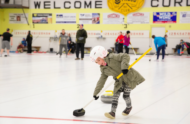 A young curler gets a taste of sweeping for the first time during the Curling Canada Rocks & Rings session November 21st at the Stroud Curling Club (Photo Ramsey Blacklock/Rock Solid Productions)