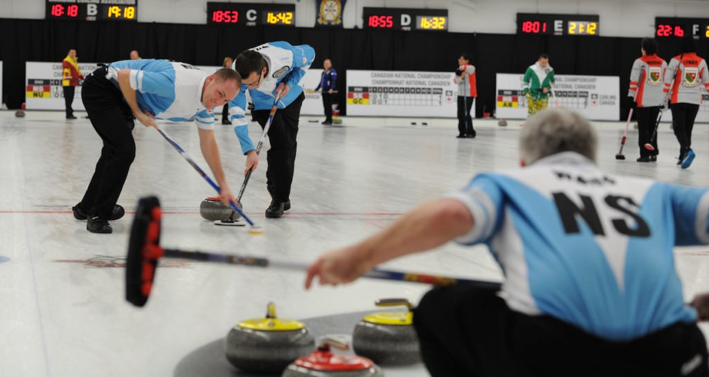 Nova Scotia sweepers Ian Wilson and Brad Wilson are hard at work while third Logan Ward calls the line during Tuesday night action at the 2015 Travelers Curling Club Championship in Ottawa (Curling Canada/Claudette Bockstael Photo)