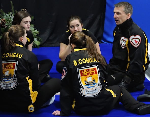 New Brunswick coach Tim Comeau, right, speaks to his team during during the fifth-end break on Monday. (Photo, Curling Canada)