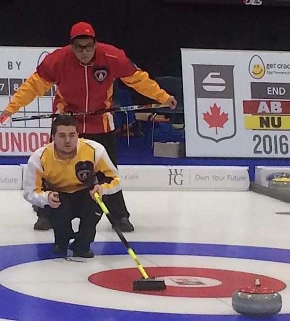 Nunavut skip Arthur Siksik peers over the shoulder of Manitoba skip Matt Dunstone during Draw 1 action on Saturday.