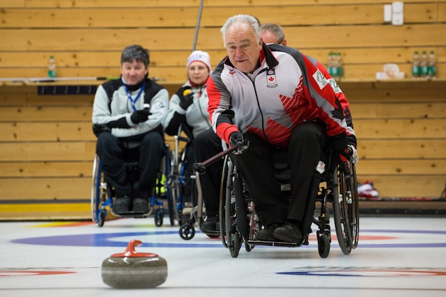 Team Canada skip Jim Armstrong delivers his rock against Norway at the World Wheelchair Curling Championship in Lucerne, Switzerland (WCF/Céline Stucki photo)