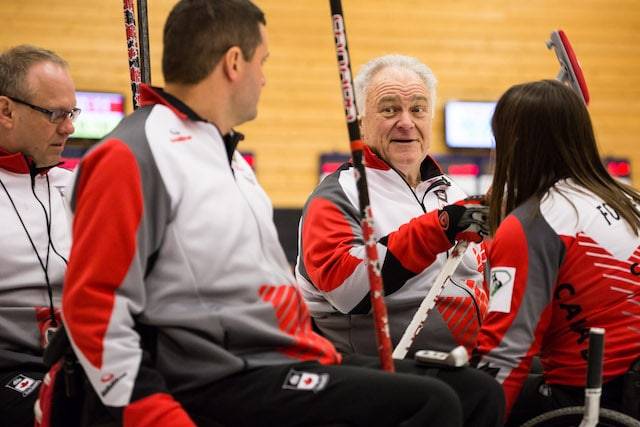 Skip Jim Armstrong and teammates (l-r) Dennis Thiessen, Mark Ideson and Ina Forrest confer during their game at the 2016 World Curling Championship in Lucerne, Switzerland (WCF/Céline Stucki photo)