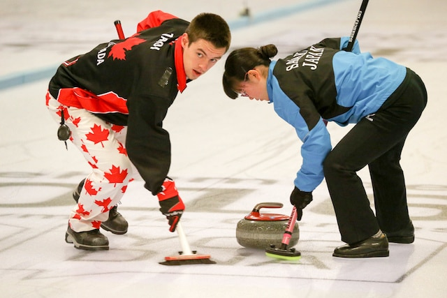 Tyler Tardi and teammate Honoka Sasaki of Japan sweep their rock to the house during Mixed Doubles play at the Youth Olympic Games in Lillehammer, Norway (WCF/Richard Gray photo)