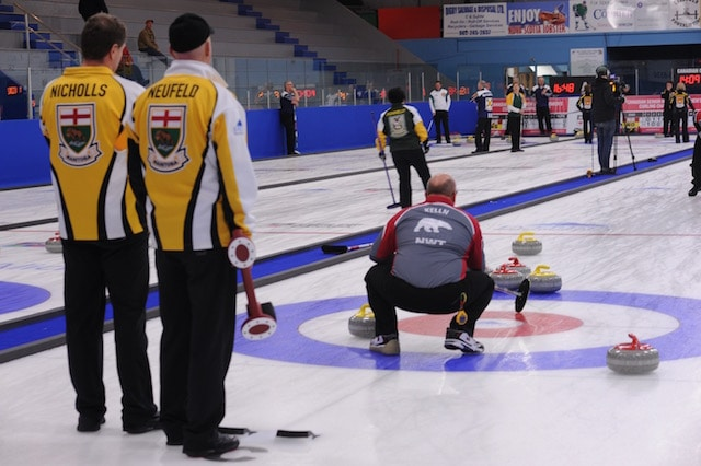 Manitoba's Randy Neufeld and Peter Nicholls watch as Northwest Territories' Brian Kelln calls the line (Curling Canada/Mike Lewis photo)