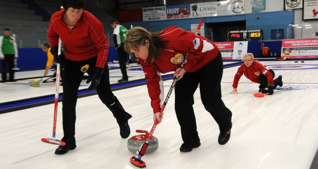 Newfoundland and Labrador skip Cathy Cunningham watches her rock as sweepers Heather Martin and Patricia Tiller take over at the 2016 Canadian Seniors Championship (Curling Canada/Mike Lewis photo)